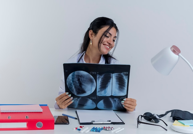 Glimlachende jonge vrouwelijke arts die medische gewaad en stethoscoopzitting bij bureau met medische hulpmiddelen draagt ?? die en x-ray geïsoleerd schot bekijken bekijkt