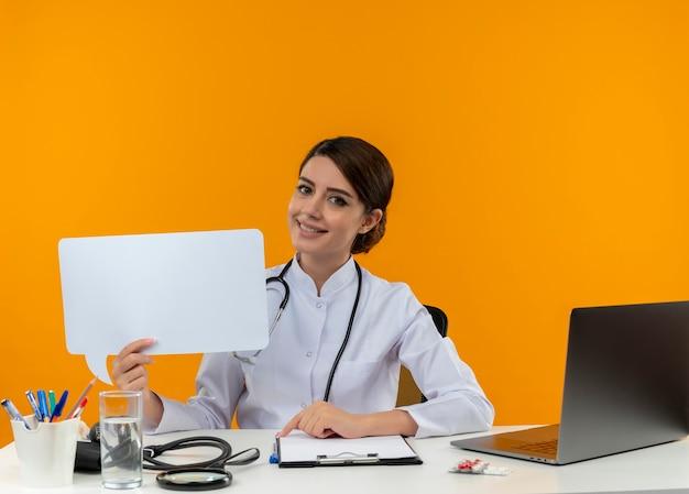 Glimlachende jonge vrouwelijke arts die medische gewaad met stethoscoop draagt die aan bureau werkt op computer met medische hulpmiddelen die praatjebel op isolatie gele achtergrond houden