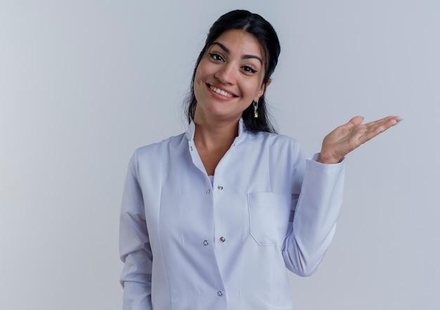 Glimlachende jonge vrouwelijke arts die medische mantel draagt die lege hand toont die geïsoleerd kijkt