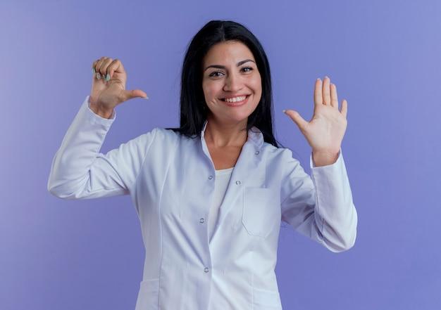 Glimlachende jonge vrouwelijke arts die medische mantel draagt die tonend zes met handen kijkt