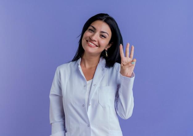 Glimlachende jonge vrouwelijke arts die medische mantel draagt die toont drie met hand kijkt