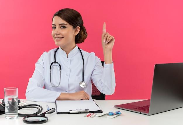 Glimlachende jonge vrouwelijke arts die medische mantel en stethoscoop draagt die aan bureau met medische hulpmiddelen en laptop zit die hand op bureau zet en omhoog wijst geïsoleerd op roze muur