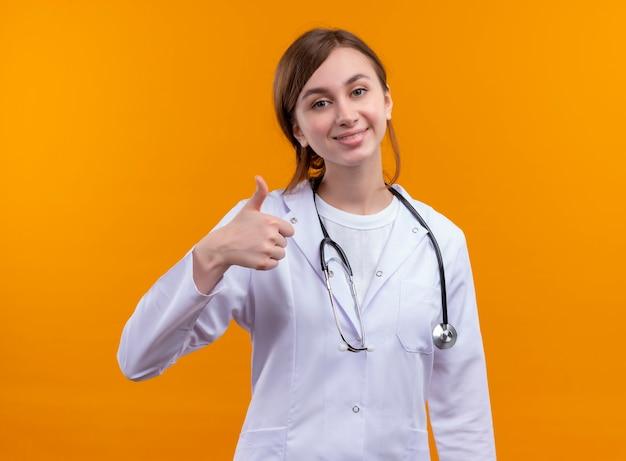 Glimlachende jonge vrouwelijke arts die medische mantel en stethoscoop draagt die duim op geïsoleerde oranje muur tonen
