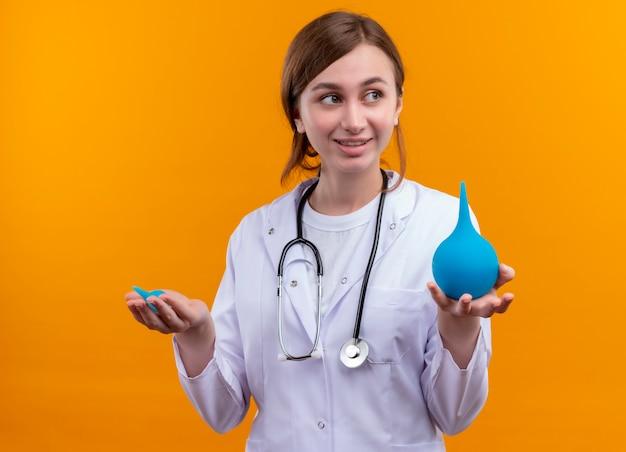 Glimlachende jonge vrouwelijke arts die medische mantel en stethoscoop draagt die klysma's op geïsoleerde oranje muur houden