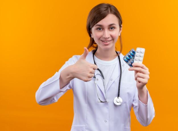 Glimlachende jonge vrouwelijke arts die medische mantel en stethoscoop draagt die medische drugs houdt en duim op geïsoleerde oranje muur toont