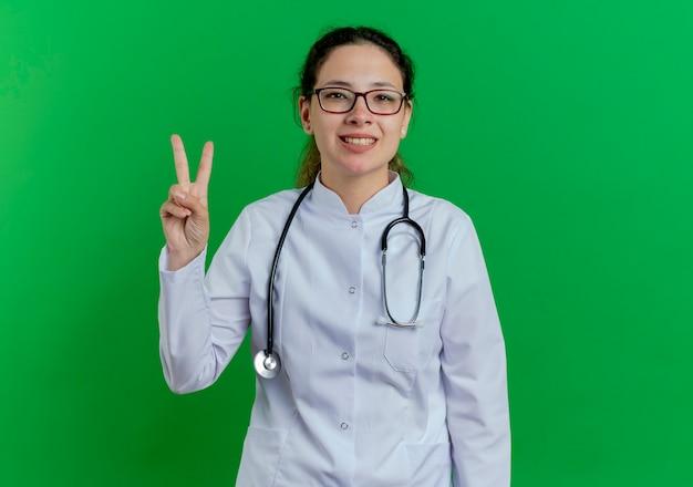 Glimlachende jonge vrouwelijke arts die medische mantel en stethoscoop en bril draagt die vredesteken doet dat op groene muur met exemplaarruimte wordt geïsoleerd