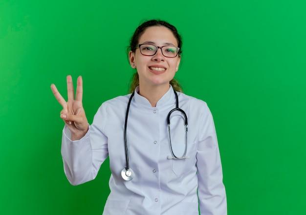 Glimlachende jonge vrouwelijke arts die medische mantel en stethoscoop en glazen draagt die drie met hand tonen die op groene muur met exemplaarruimte wordt geïsoleerd