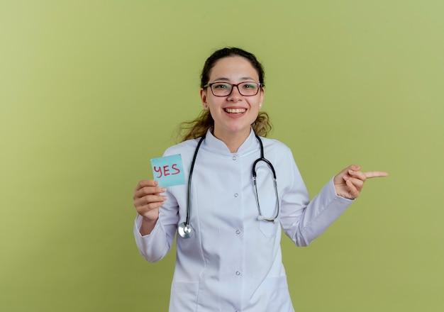 Glimlachende jonge vrouwelijke arts die medische mantel en stethoscoop met bril draagt die document notapunten aan geïsoleerde kant houdt