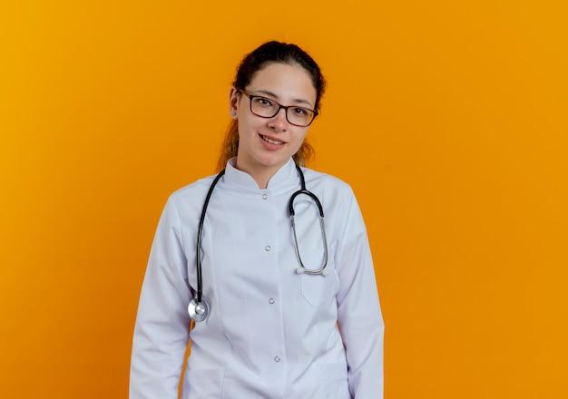 Glimlachende jonge vrouwelijke arts die medische mantel en stethoscoop met geïsoleerde bril draagt