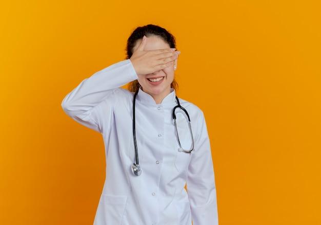 Glimlachende jonge vrouwelijke arts die medische mantel en stethoscoop met glazen draagt die met geïsoleerde handogen wordt behandeld