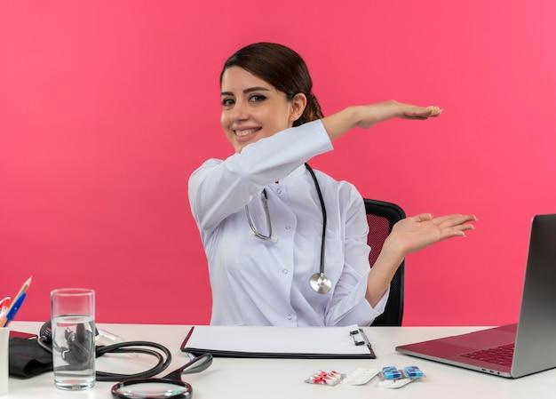 Glimlachende jonge vrouwelijke arts die medische mantel met een stethoscoop zit aan het bureau werkt op computer met medische hulpmiddelen die grootte met exemplaarruimte tonen