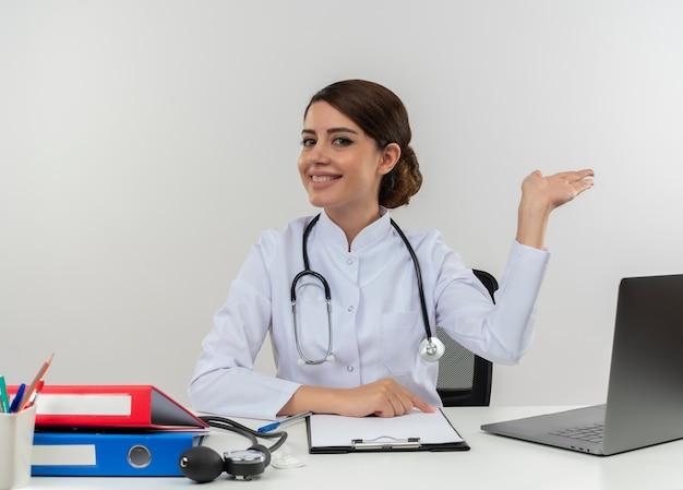Glimlachende jonge vrouwelijke arts die medische mantel met een stethoscoop zittend aan een bureau werkt op de computer met medische hulpmiddelen prettending houden iets met kopie ruimte