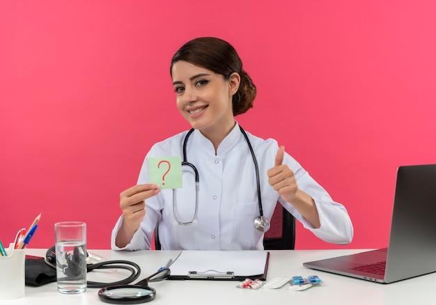 Glimlachende jonge vrouwelijke arts die medische mantel met stethoscoop draagt die aan bureau zit werkt op computer met medische hulpmiddelen die vraagteken houdt markeert haar duim omhoog op roze muur
