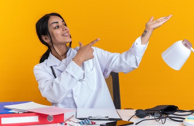 Glimlachende jonge vrouwelijke arts die medische mantel met stethoscoop draagt, zit aan tafel met medische hulpmiddelen die doen alsof ze vasthouden en wijzen naar iets geïsoleerd op gele achtergrond