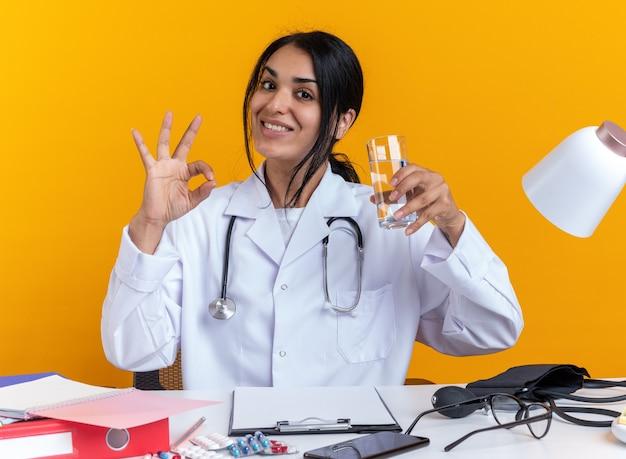 Glimlachende jonge vrouwelijke arts die medische mantel met stethoscoop draagt, zit aan tafel met medische hulpmiddelen met glas water met goed gebaar geïsoleerd op gele achtergrond