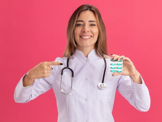 Glimlachende jonge vrouwelijke arts die medische mantel met stethoscoopholding draagt en wijst op pillen die op roze muur worden geïsoleerd