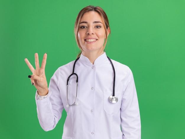 Glimlachende jonge vrouwelijke arts die medische robe met stethoscoop draagt die drie toont die op groene muur worden geïsoleerd