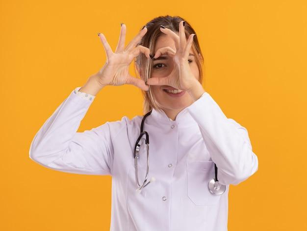 Glimlachende jonge vrouwelijke arts die medische robe met stethoscoop draagt die hartgebaar toont dat op gele muur wordt geïsoleerd