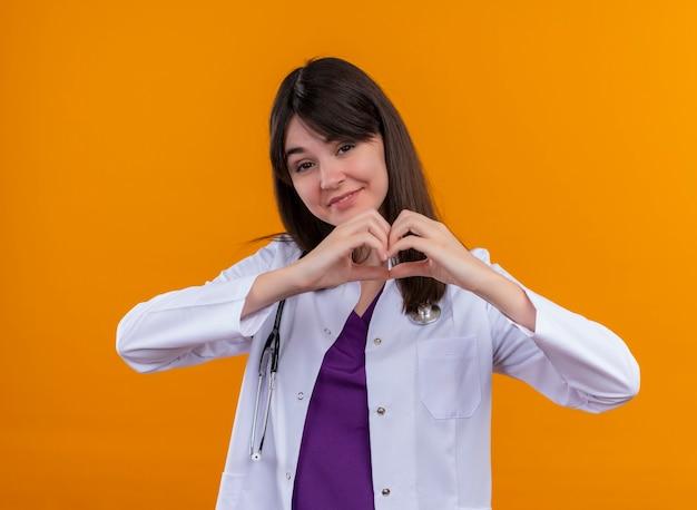 Glimlachende jonge vrouwelijke arts in medisch kleed met het hart van stethoscoopgebaren met beide handen op geïsoleerde oranje achtergrond met exemplaarruimte