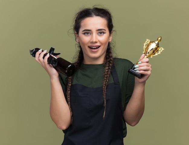 Glimlachende jonge vrouwelijke kapper in uniform bedrijf winnaar beker met tondeuse geïsoleerd op olijfgroene muur
