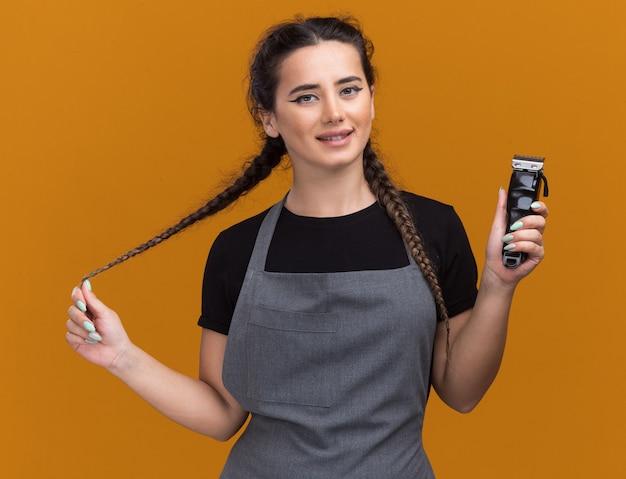 Glimlachende jonge vrouwelijke kapper in uniform met tondeuses en greep haar geïsoleerd op oranje muur