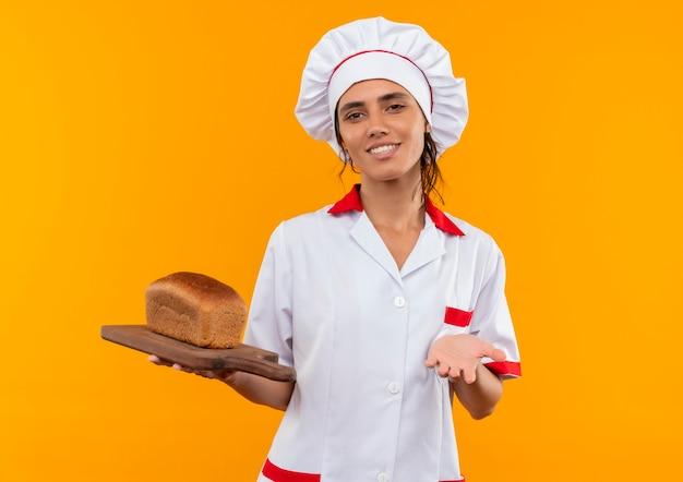 Glimlachende jonge vrouwelijke kok die brood van de chef-kok het eenvormige bedrijf op scherpe raad met exemplaarruimte draagt