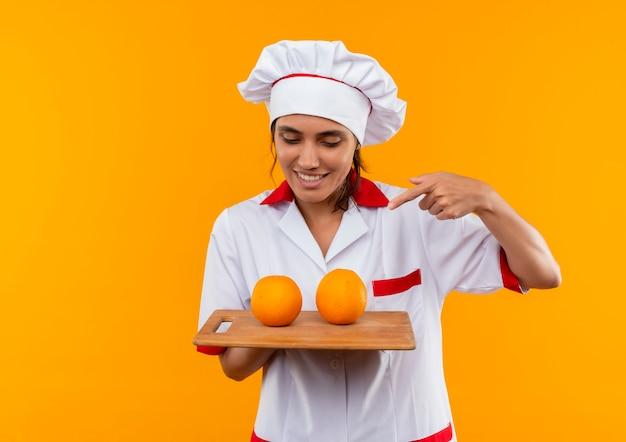 Glimlachende jonge vrouwelijke kok die chef-kok eenvormige holding draagt en naar sinaasappel op scherpe raad met exemplaarruimte wijst