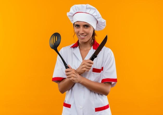 Glimlachende jonge vrouwelijke kok die chef-kok eenvormige holding draagt en spatel en mes met exemplaarruimte kruist