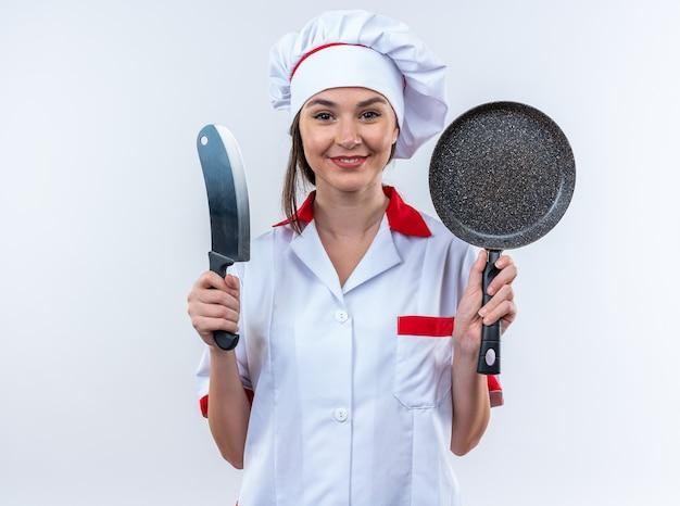 Glimlachende jonge vrouwelijke kok die chef-kok uniform draagt die pan met hakmes houdt die op witte achtergrond wordt geïsoleerd