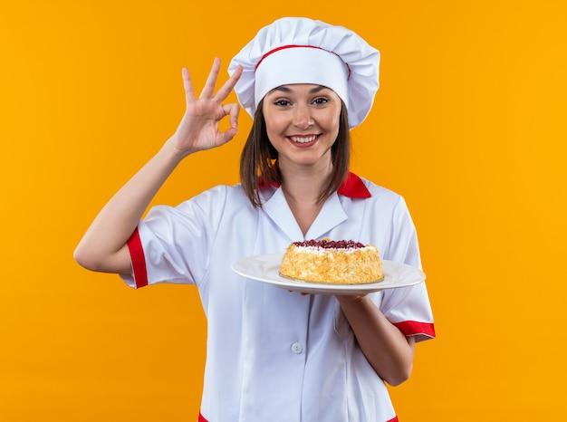 Glimlachende jonge vrouwelijke kok die chef-kokuniform draagt die cake op plaat houdt die oke gebaar toont dat op oranje muur wordt geïsoleerd