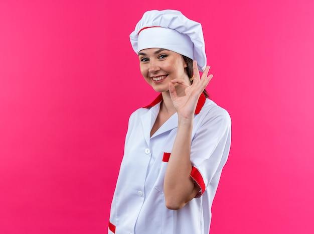 Glimlachende jonge vrouwelijke kok die chef-kokuniform draagt die oke gebaar toont dat op roze muur wordt geïsoleerd