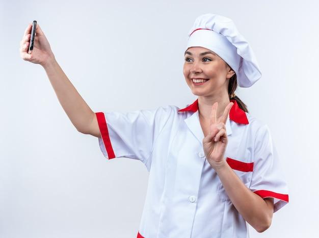 Glimlachende jonge vrouwelijke kok die chef-kokuniform draagt, neemt een selfie met vredesgebaar geïsoleerd op een witte muur