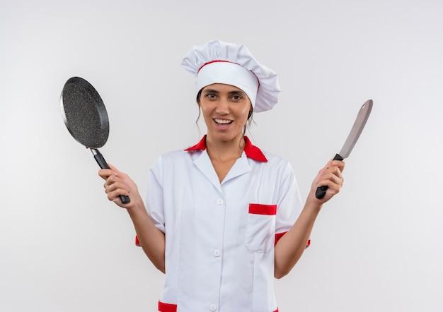 Glimlachende jonge vrouwelijke kok die de koekenpan en het hakmes van de chef-kok eenvormige holding met exemplaarruimte draagt Gratis Foto