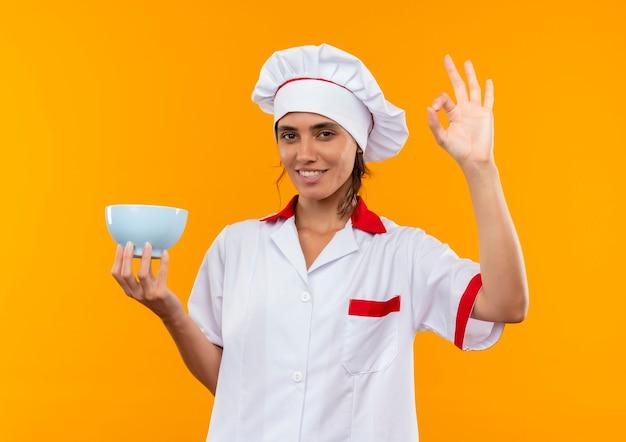 Glimlachende jonge vrouwelijke kok die de kom van de chef-kok eenvormige holding draagt en okey gebaar toont