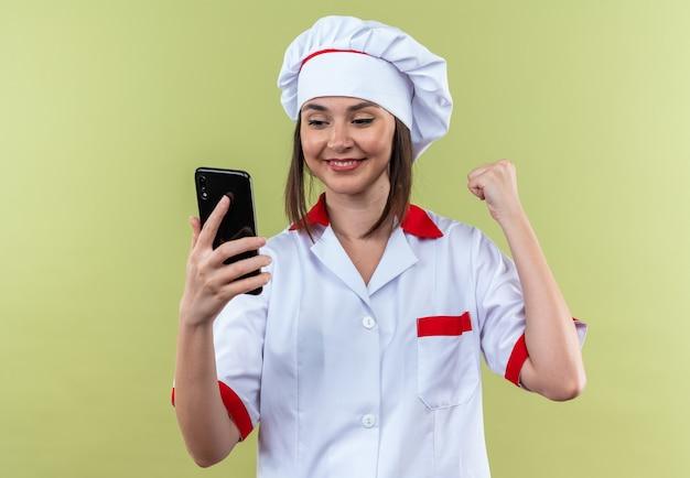 Glimlachende jonge vrouwelijke kok die een chef-kokuniform draagt en naar de telefoon kijkt met een ja-gebaar dat op een olijfgroene muur wordt geïsoleerd