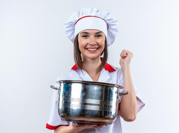 Glimlachende jonge vrouwelijke kok die een uniforme chef-kok draagt die een steelpan toont die ja gebaar toont dat op witte achtergrond wordt geïsoleerd