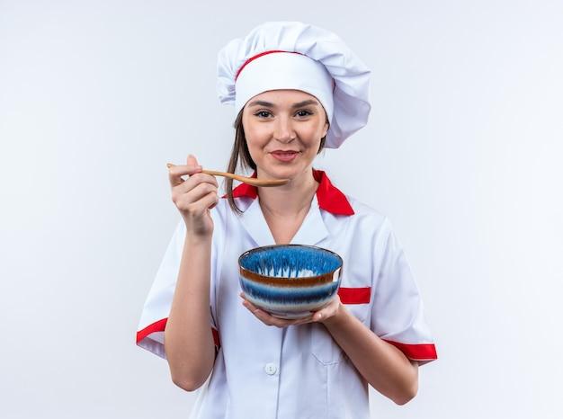 Glimlachende jonge vrouwelijke kok die een uniforme chef-kok draagt die kom met lepel draagt die op witte muur wordt geïsoleerd