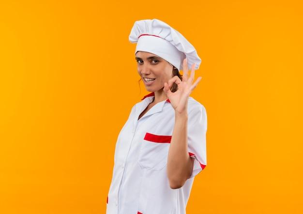 Glimlachende jonge vrouwelijke kok die eenvormige chef-kok draagt die okgebaar met exemplaarruimte toont