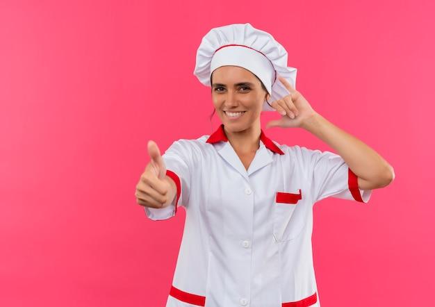 Glimlachende jonge vrouwelijke kok die eenvormige chef-kok draagt die telefoongesprek toont en je gebaar met exemplaarruimte