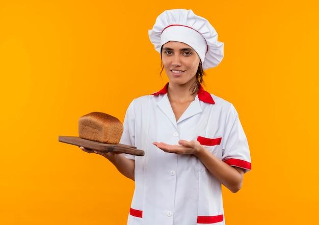 Glimlachende jonge vrouwelijke kok die eenvormige chef-kok draagt ?? en met hand aan brood op scherpe raad met exemplaarruimte toont