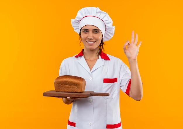 Glimlachende jonge vrouwelijke kok die het brood van de chef-kok eenvormig bedrijf op scherpe raad draagt en okey gebaar met exemplaarruimte toont