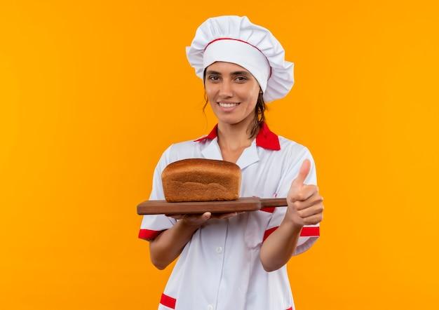 Glimlachende jonge vrouwelijke kok die het brood van de chef-kok eenvormig bedrijf op scherpe raad haar duim met exemplaarruimte draagt