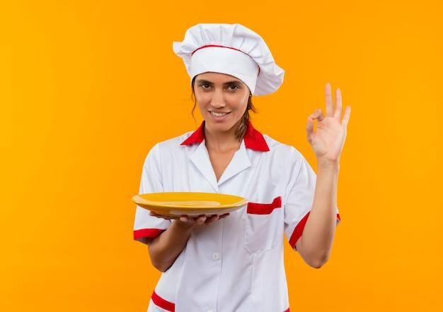 Glimlachende jonge vrouwelijke kok die plaat van de chef-kok de eenvormige holding draagt en okeygebaar met exemplaarruimte toont