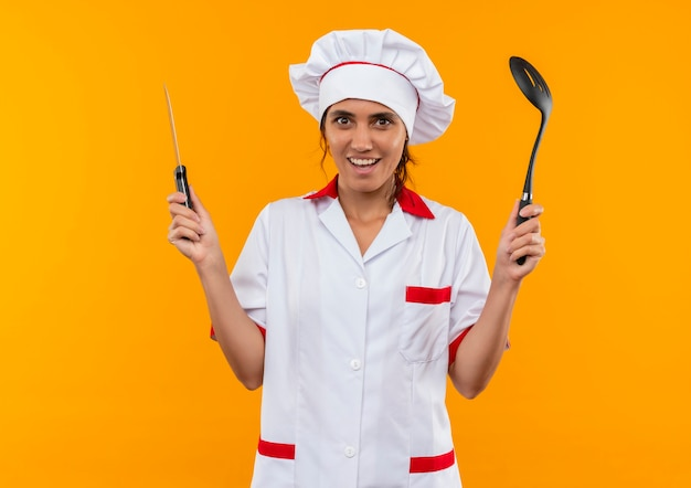 Glimlachende jonge vrouwelijke kok die spatel en mes van de chef-kok eenvormig bedrijf met exemplaarruimte draagt