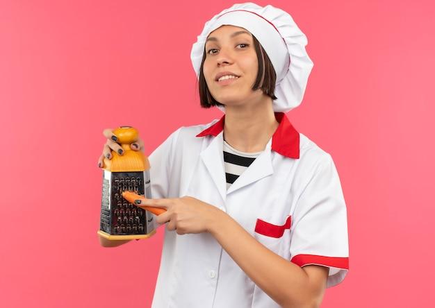 Glimlachende jonge vrouwelijke kok in chef-kok uniforme rasp wortel met rasp geïsoleerd op roze muur