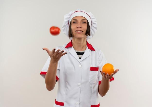 Glimlachende jonge vrouwelijke kok in de eenvormige sinaasappel van de chef-kok houden en het werpen van tomaat die op witte muur wordt geïsoleerd