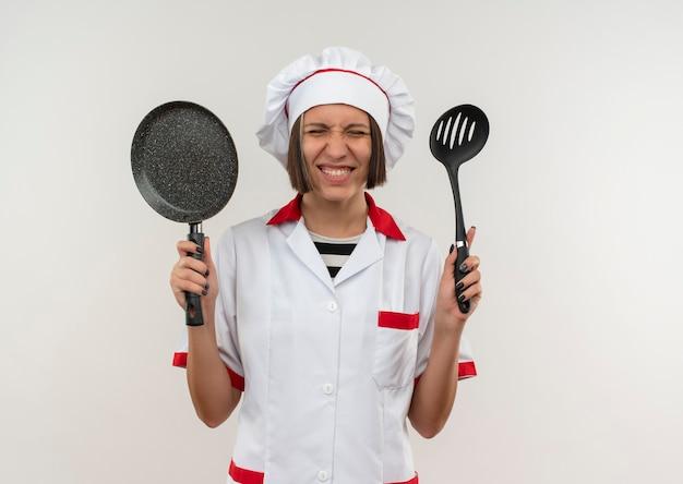 Glimlachende jonge vrouwelijke kok in de eenvormige spatel en de koekenpan van de chef-kok die met gesloten ogen op witte muur worden geïsoleerd