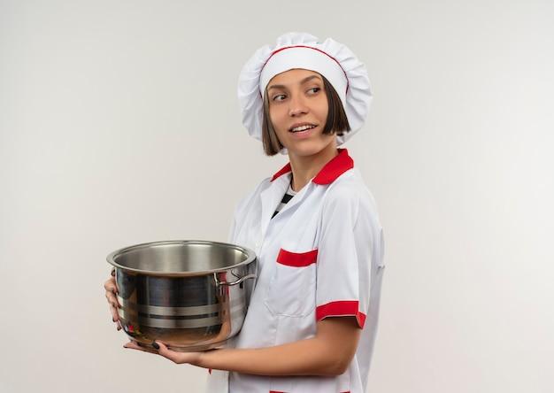 Glimlachende jonge vrouwelijke kok in de pot van de chef-kok de eenvormige holding en het bekijken kant die op witte muur wordt geïsoleerd