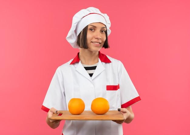 Glimlachende jonge vrouwelijke kok in de snijplank van de chef-kok eenvormige bedrijf met sinaasappelen daarop geïsoleerd op roze muur