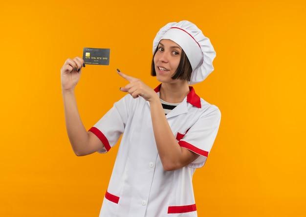 Glimlachende jonge vrouwelijke kok in eenvormige chef-kok die en op creditcard houdt die voorzijde bekijkt die op oranje muur wordt geïsoleerd